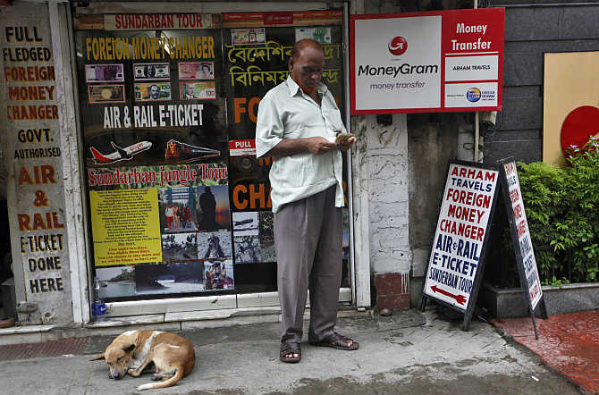 A customer counts currency outside a currency exchange shop in Kolkata.