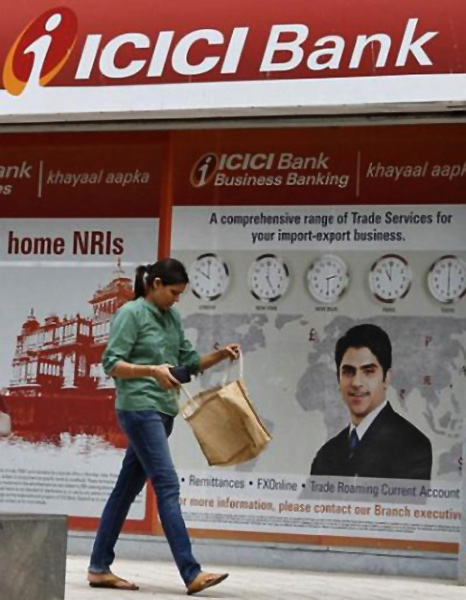 A woman passes by the ICICI Bank.