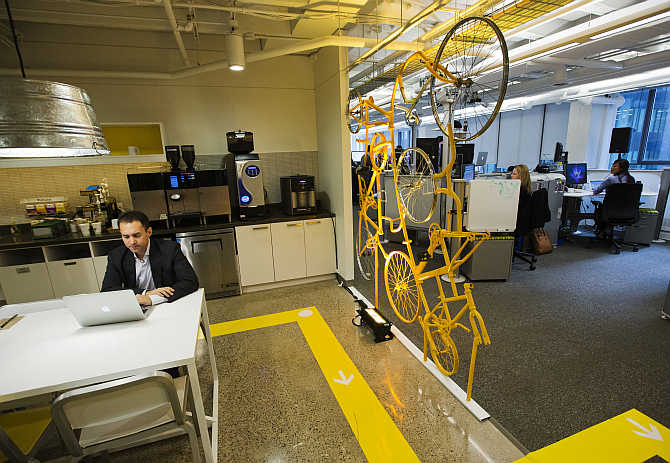 An employee works in the kitchen beside a structure made of recycled bicycles at the Google office in Toronto, Canada.