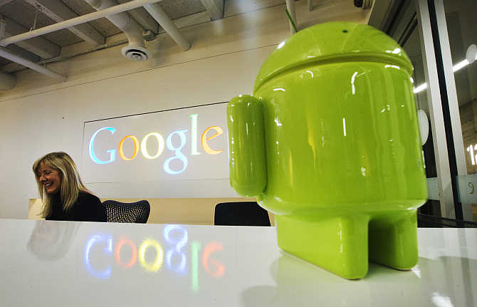 A Google Android figurine sits on the welcome desk as employee Tracy McNeilly smiles at the Google office in Toronto, Canada.