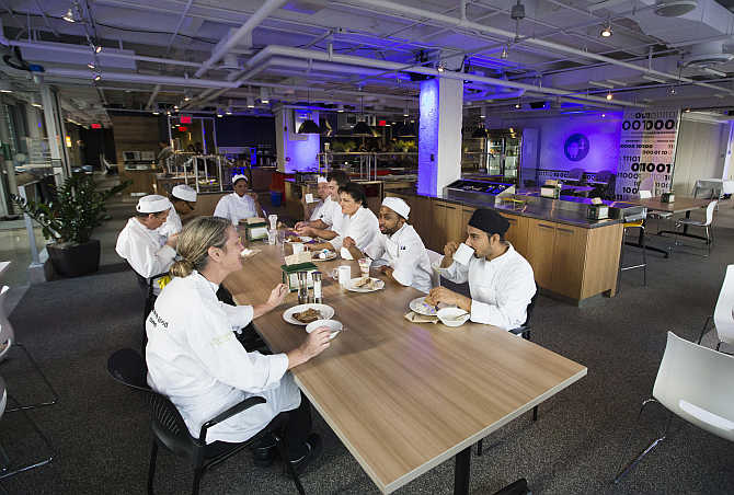 Food preparation team sit down to eat at the Google office in Toronto, Canada.