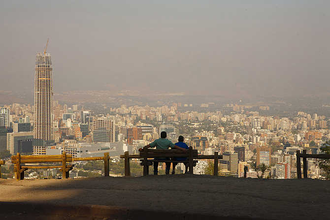 A man sits with his son while enjoying the view of the Andes Mountains Range at the San Cristobal Hill in Santiago de Chile, Chile.