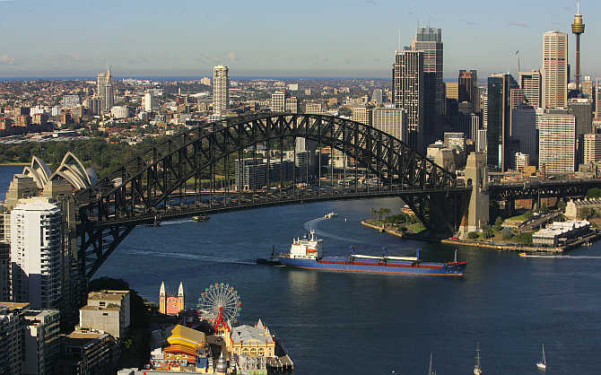 A cargo ship sails under the Sydney Harbour Bridge on its way in to port June, Australia.