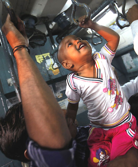 A child tries to hold onto the handrails in a crowded suburban train.