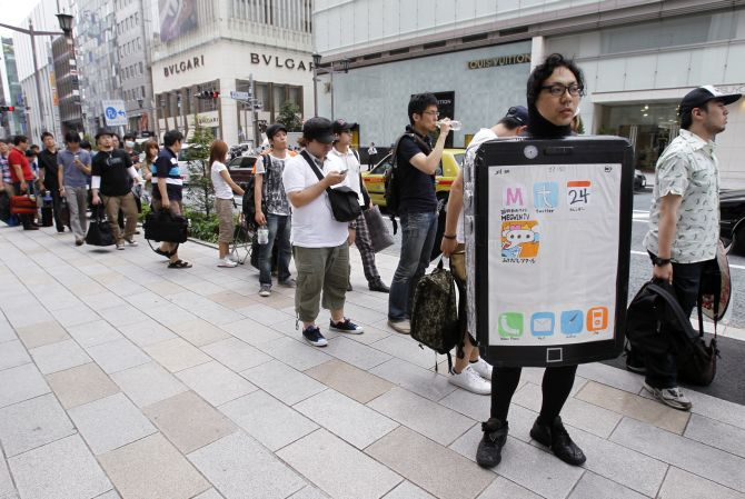 Customers waiting for the release of the new iPhone 4 line up outside Apple Inc's store in the Ginza district of Tokyo.