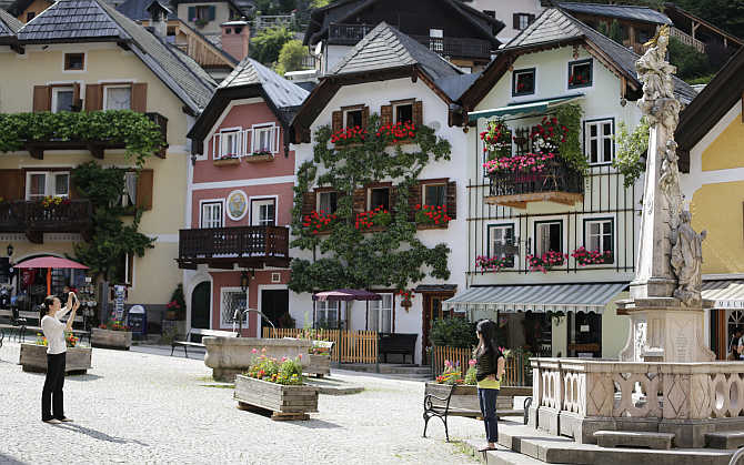 Tourists photograph each other in the Austrian world heritage village of Hallstatt.