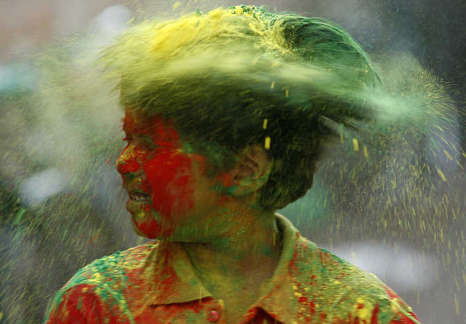 A boy shakes his head to remove coloured powder while celebrating Holi in Agartala.