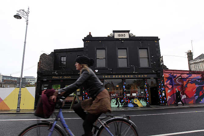 A woman cycles past the 'Coffee To Get Her' restaurant near Dublin city centre which becomes a bar and club in the evenings, Ireland.
