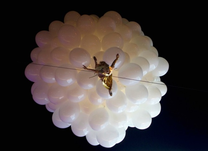 An artist hanging from balloons performs during the opening of Esentai Mall in Almaty, Kazakhstan.