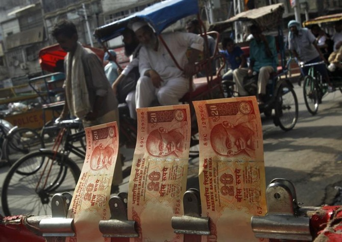 Cycle rickshaws move past a display of rupee notes at a roadside currency exchange stall in Delhi.