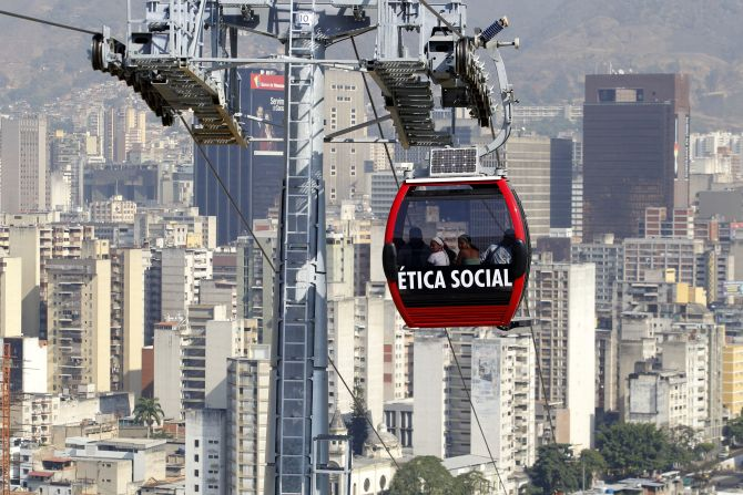 Commuters travel in a Metrocable cabin in Caracas. The Caracas Metrocable cable car starts operations over 1.8 km (0.93 miles) with five stops through the upper slum districts.