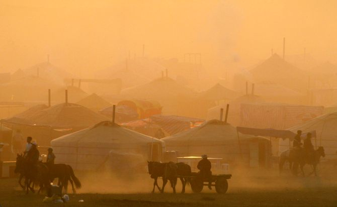Mongolian horsemen pass a row of traditional tent houses known as ger near a horse race venue during the Naadam Festival at Khui Doloon Khudag village, some 35 kms (21 miles) outside the capital Ulan Bator.