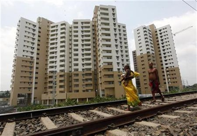 A woman carrying a child walks ahead of her husband on a railway track in front of residential buildings under construction on the outskirts of Kolkata.