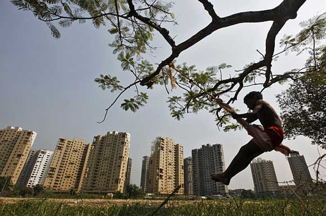 A boy plays on a swing in front of a residential estate in Kolkata.