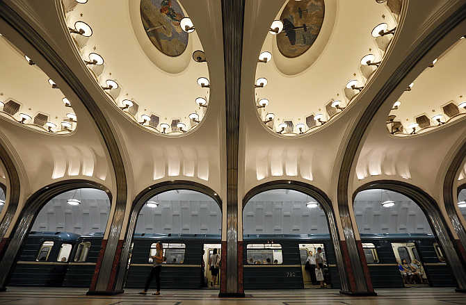 A woman walks on the platform as a train arrives at Mayakovskaya metro station in Moscow, Russia.