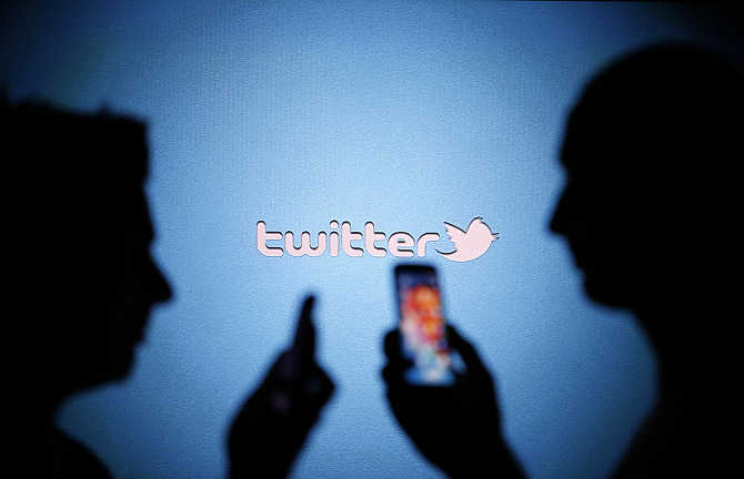 Men are silhouetted against a video screen with a Twitter logo in the central Bosnian town of Zenica.