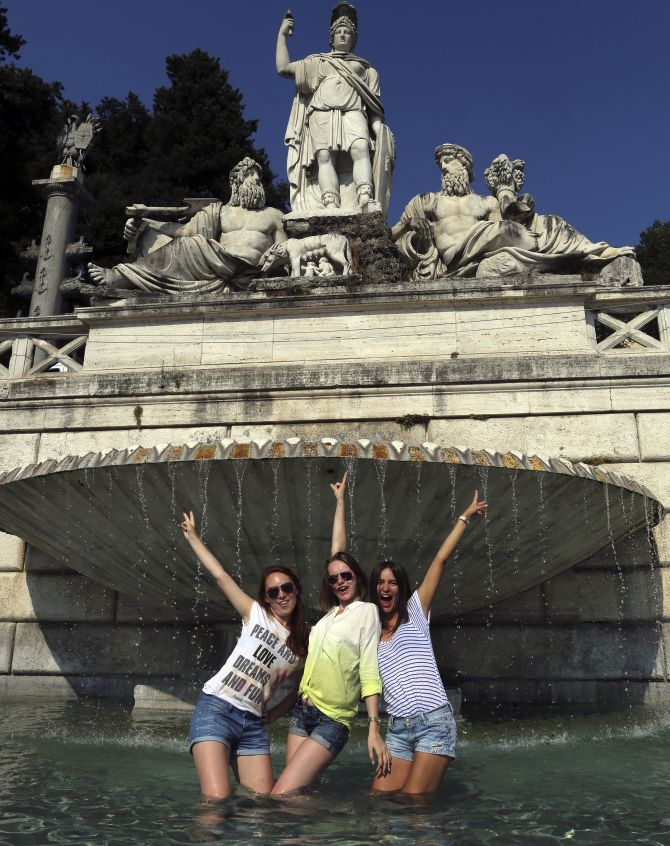 Girls pose for a picture in a fountain on a hot summer's day in Rome.