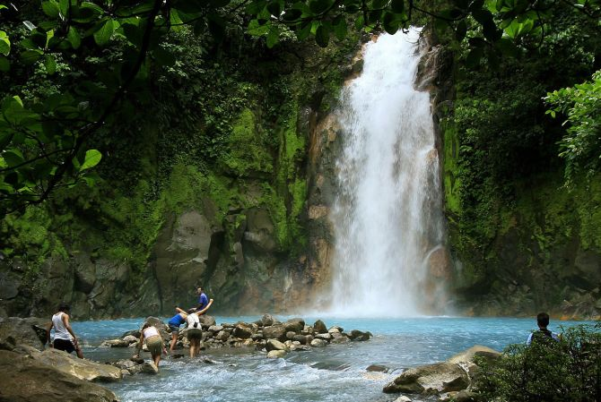 People swim in the Celeste river waterfall at Tenorio Volcano National Park in Upala.