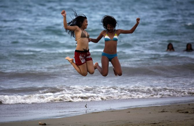 Tourists jump as they enjoy a day on the beach in Cabarete.