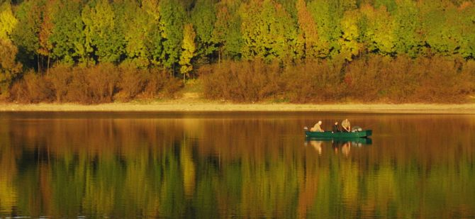Fishermen silently sit in their boat, camouflaged by the colours of the fall, waiting for their catch at Liptovska Mara dam, Slovakia's favorite fishing destination.