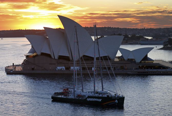 The new Greenpeace Rainbow Warrior ship navigates past the Sydney Opera House.
