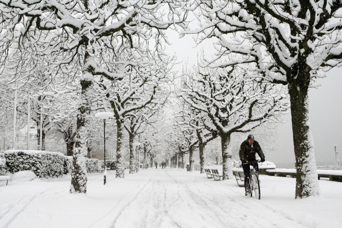A man cycles during snowfall in Zurich.
