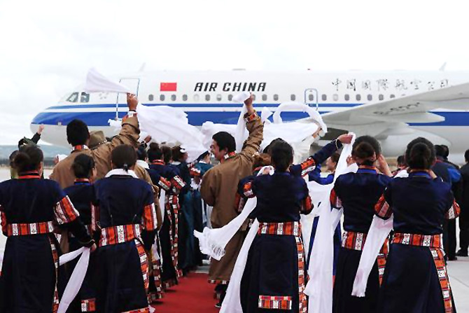 Local Tibetans wave hada, or traditional silk scarves, as they greet the first group of passengers who landed at Daocheng Yading Airport.