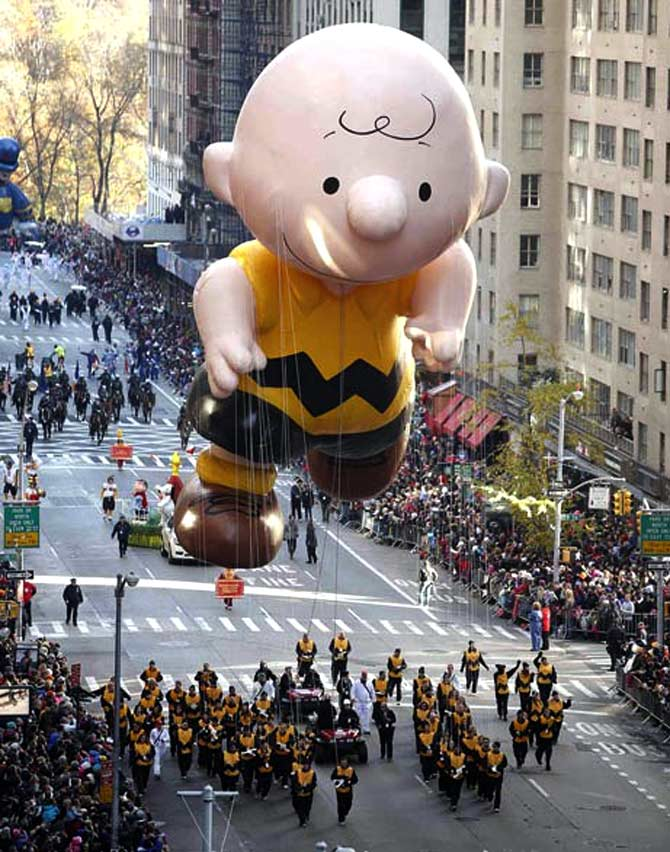 A Charlie Brown balloon floats make their way down 6th Ave during the Macy's Thanksgiving Day Parade in New York.