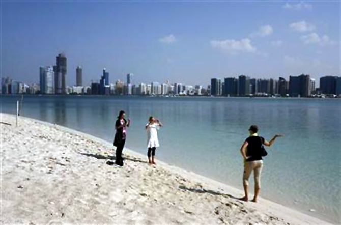 A tourist takes a photograph in front of the skyline of Abu Dhabi.