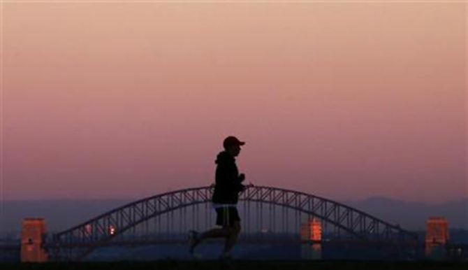 A man runs across a hill in front of the Sydney Harbour Bridge under a smoke tinted sky at daybreak.