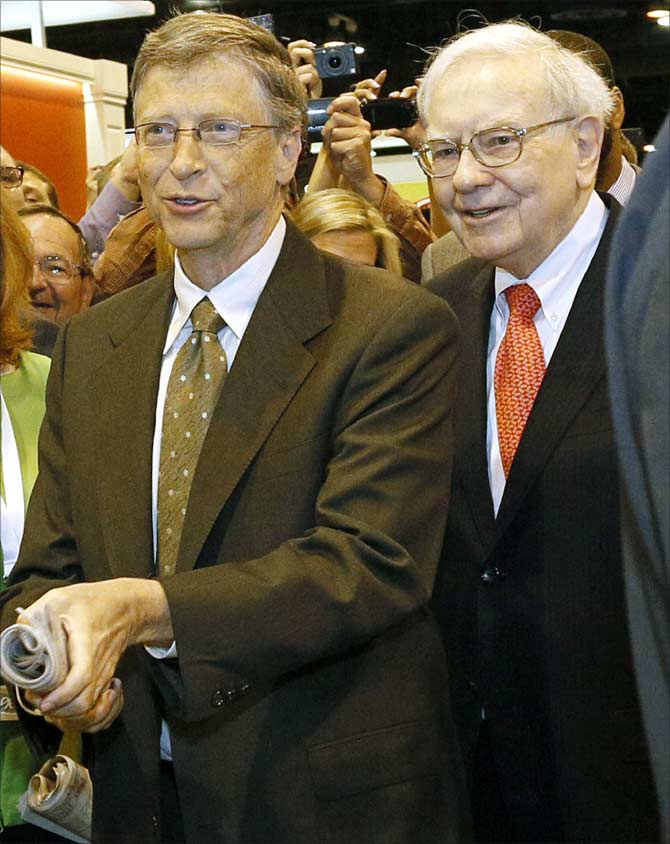 Berkshire Hathaway CEO Warren Buffett (R) watches Microsoft Chairman Bill Gates prepare to throw a newspaper in a competition just before Berkshire Hathaway's annual meeting in Omah