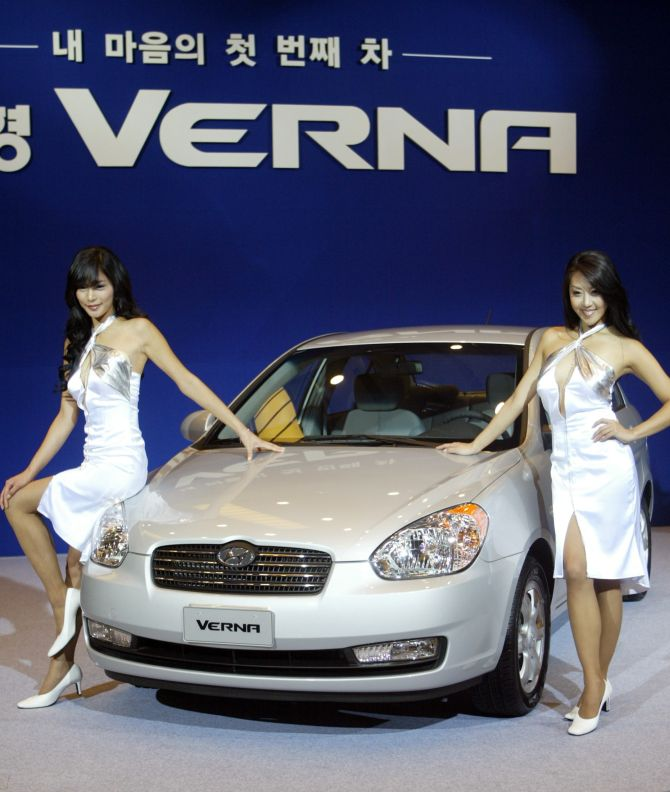 South Korean models pose next to Hyundai Motors' New Verna at its unveiling ceremony in Seoul.