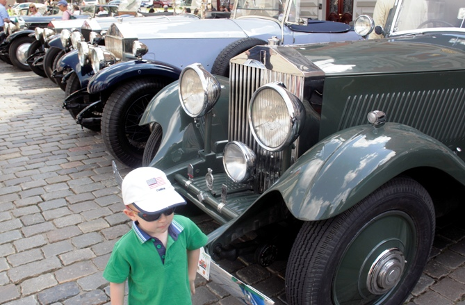 A boy walks past vintage Rolls-Royce cars during the 20-Ghost Club Nordic and Baltic tour in Riga.