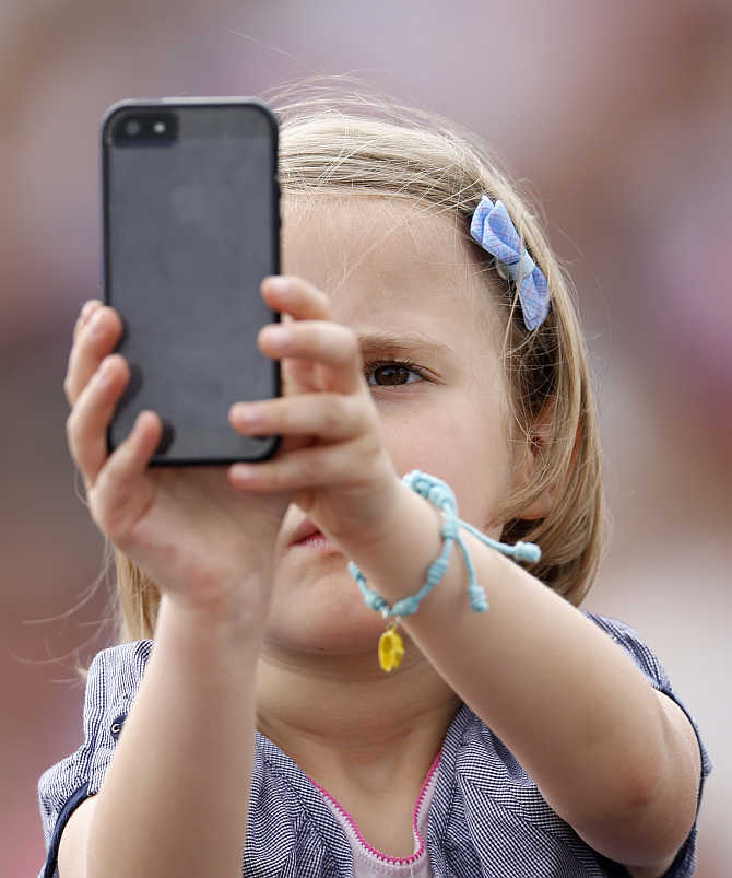 A child takes pictures with a mobile phone as Pope Francis leads the Angelus prayer from a window of the Apostolic Palace in Saint Peter's Square at the Vatican.
