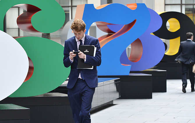 A worker uses his mobile phone as he walks past sculptures in the City of London.