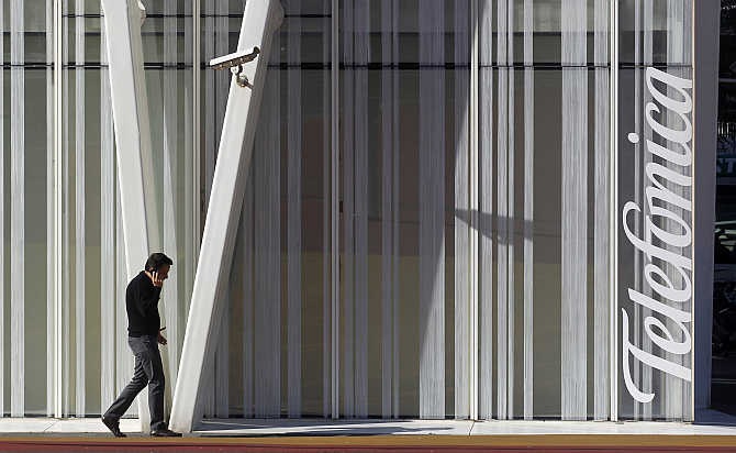 A man speaks on a mobile phone next to Telefonica's tower in Barcelona, Spain.