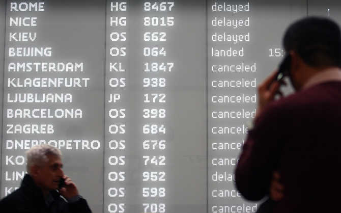 Men talk on their mobile phones while standing in front of an electronic information board at Vienna airport, Austria.