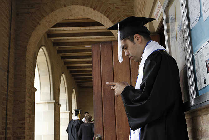 A University of California Los Angeles student checks his mobile phone in Los Angeles, California.
