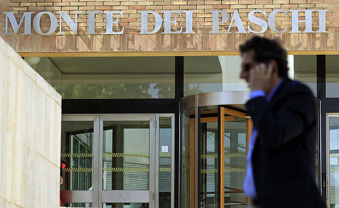 A man speaks on a mobile phone outside Monte dei Paschi bank in Siena, Italy.