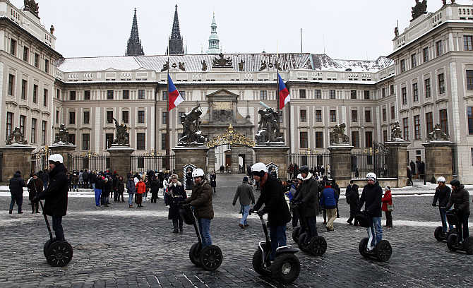 Tourists ride segways past Prague Castle in the Czech Republic.