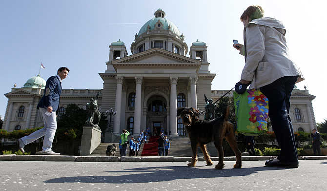 A woman with a dog stands in front of the Parliament building in Belgrade, Serbia.