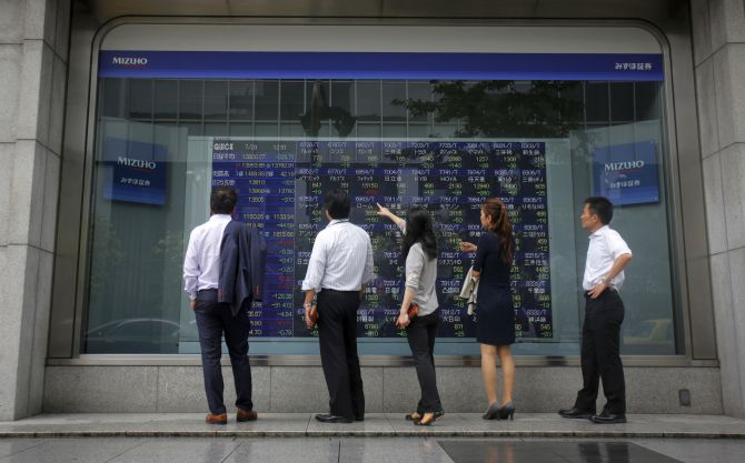 Pedestrians stand in front of a stock quotation board displaying various stock prices outside a brokerage in Tokyo.