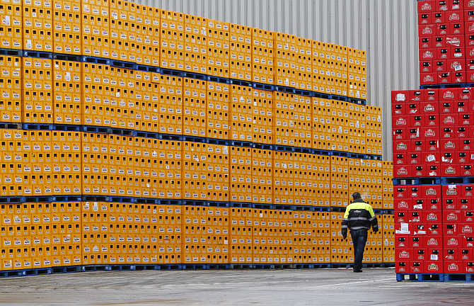 A worker inspects racks of beer bottles at the Anheuser-Busch InBev's plant in Jupille near Liege, Belgium.