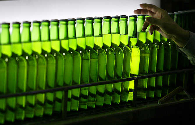 A man picks a bottle at an assembly line inside the Taiwan Beer factory in Jhunan, Miaoli County.