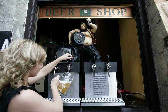 A waitress pours a pint of beer during the annual Belgian beer weekend at the Grand Place in Brussels, Belgium.