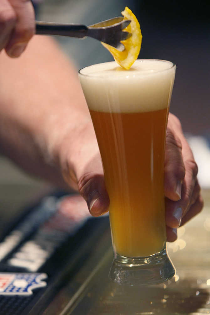 A bartender adds a slice of orange to a Blue Moon Ale for a tourist in Golden, Colorado.