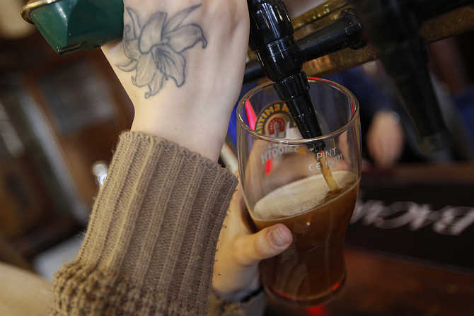 A barmaid pours a pint of beer at The Builders Arms pub in east London.