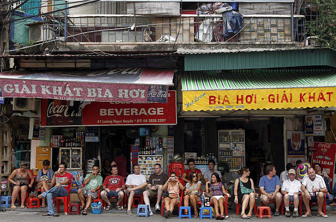 Tourists sit on stools and drink beer outside a beverage shop along a street at the old quarters in Hanoi, Vietnam.