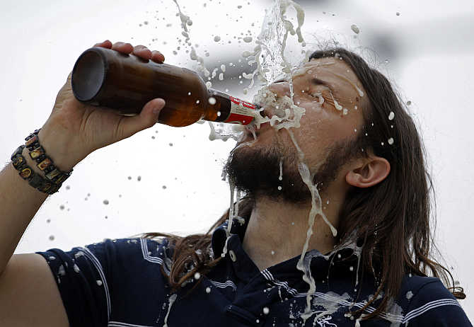 A man drinks a beer during during a wrestling show in Budapest, Hungary.