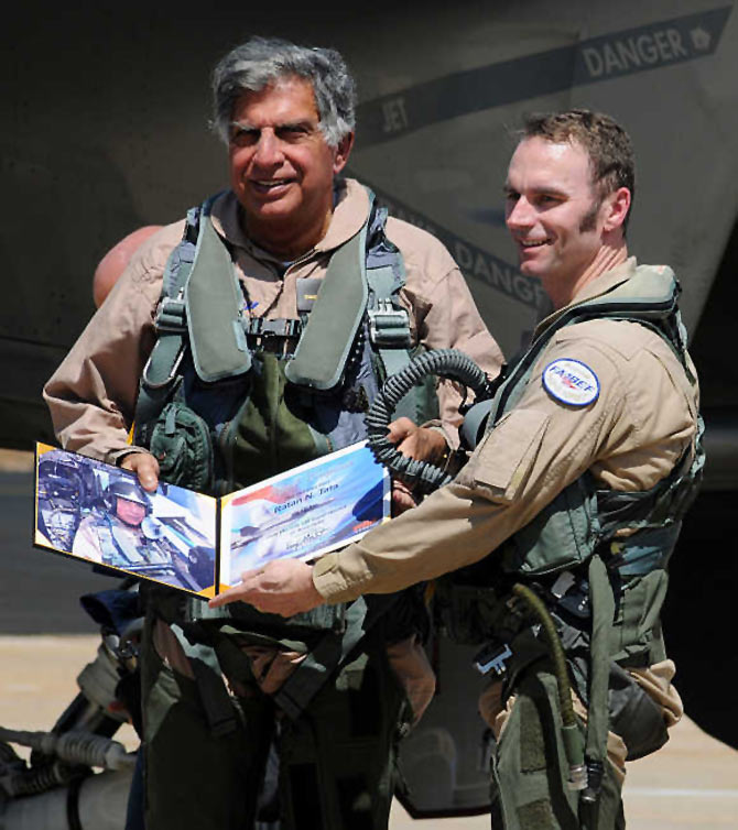 Ratan Tata receives a flight certificate by pilot Mike Wallace after they flew the F/A-18 Super Hornet aircraft during the 'Aero Ind